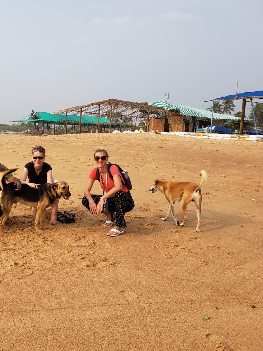 Claudia and Alyssa with free-roaming dogs on the beach, an unfinished seasonal beach shack in the background.