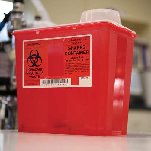 An approved sharps container is made of thick, puncture-proof plastic with a sealable lid.